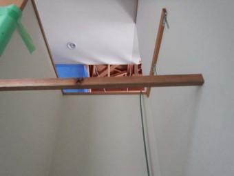 階段上部の新設収納部分の高さを棒を架けて圧迫感がないか確認しています